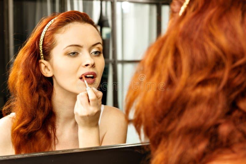 Mujer pelirroja hermosa con el lápiz labial rojo delante del espejo en cuarto de baño imagen de archivo