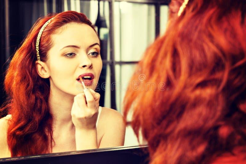 Mujer pelirroja hermosa con el lápiz labial rojo delante del espejo en cuarto de baño fotografía de archivo