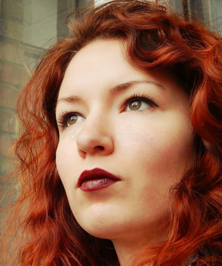 Mujer pelirroja hermosa con el pelo rizado y los labios de Borgoña fotografía de archivo