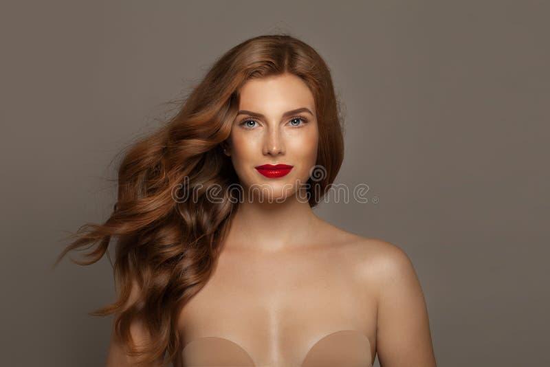 Mujer pelirroja hermosa Muchacha elegante del pelirrojo con el pelo rizado y maquillaje elegante foto de archivo