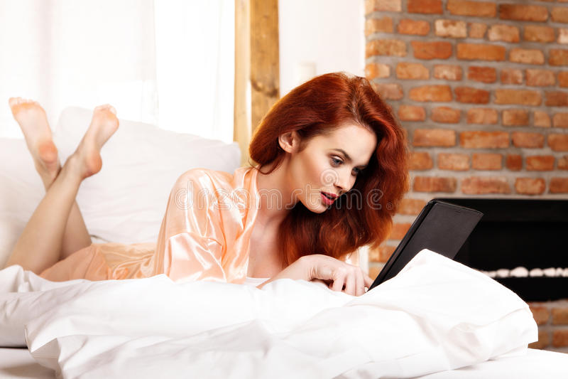 Mujer pelirroja hermosa que usa la tableta en la cama imagen de archivo