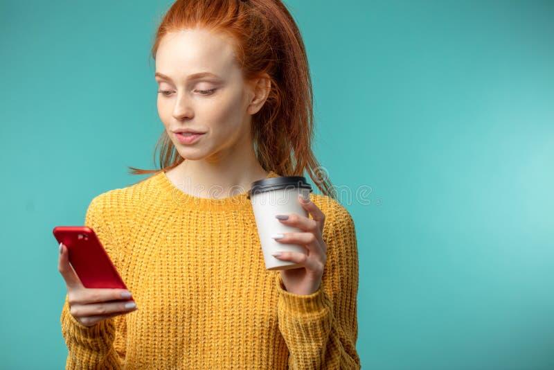 Mujer pelirroja joven con café y smartphone aislados sobre fondo azul fotos de archivo