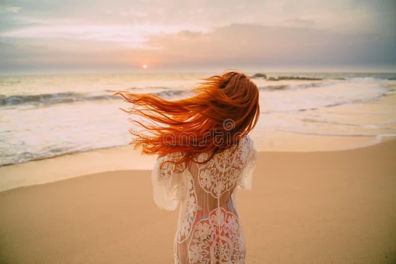 Mujer pelirroja joven con el pelo en el océano, vista posterior del vuelo imágenes de archivo libres de regalías