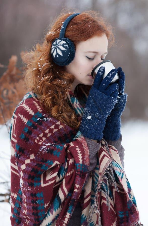 Mujer pelirroja joven en auriculares y guantes azules fotografía de archivo libre de regalías
