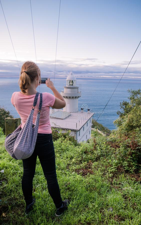 Mujer pelirroja joven que toma las fotos del paisaje marino hermoso con el faro en la costa costa atlántica, San Sebastián fotos de archivo libres de regalías