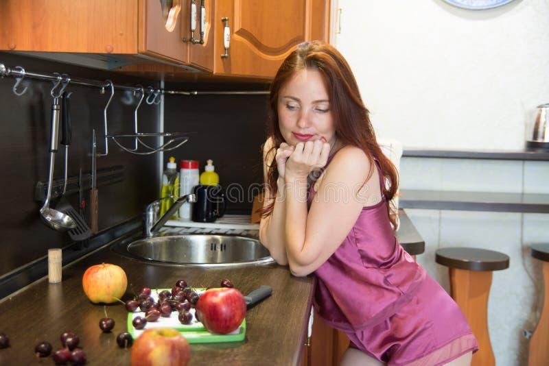 Mujer pelirroja pensativa en la cocina Señora y manzanas adultas con la cereza en la tabla fotografía de archivo libre de regalías