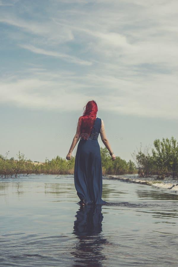 Mujer pelirroja que camina en el río imagen de archivo