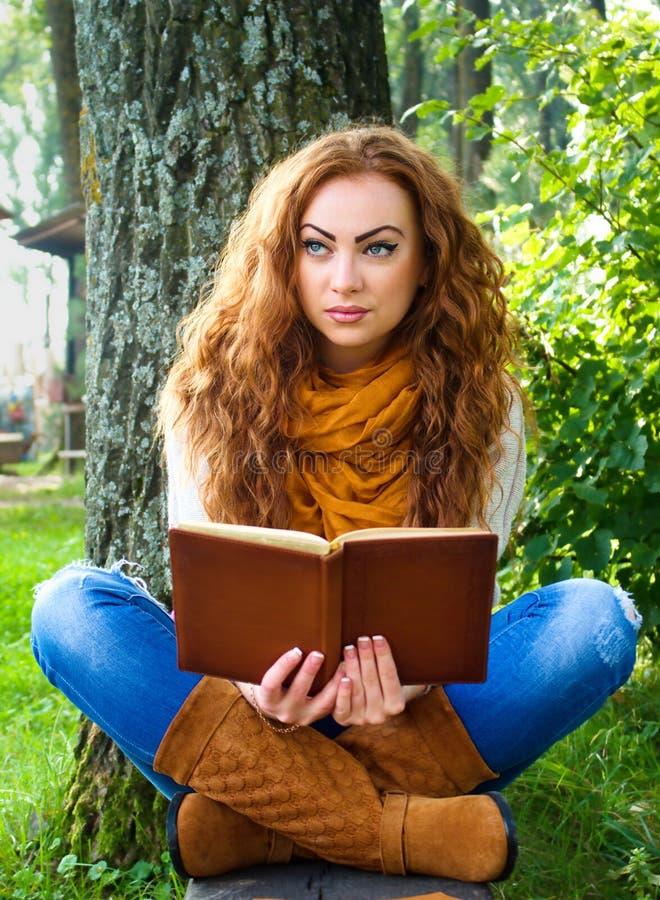 Mujer pelirroja que lee un libro en el parque que se sienta en el banco fotos de archivo libres de regalías