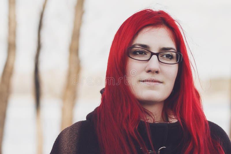 Mujer pelirroja que se coloca cerca del río imagenes de archivo