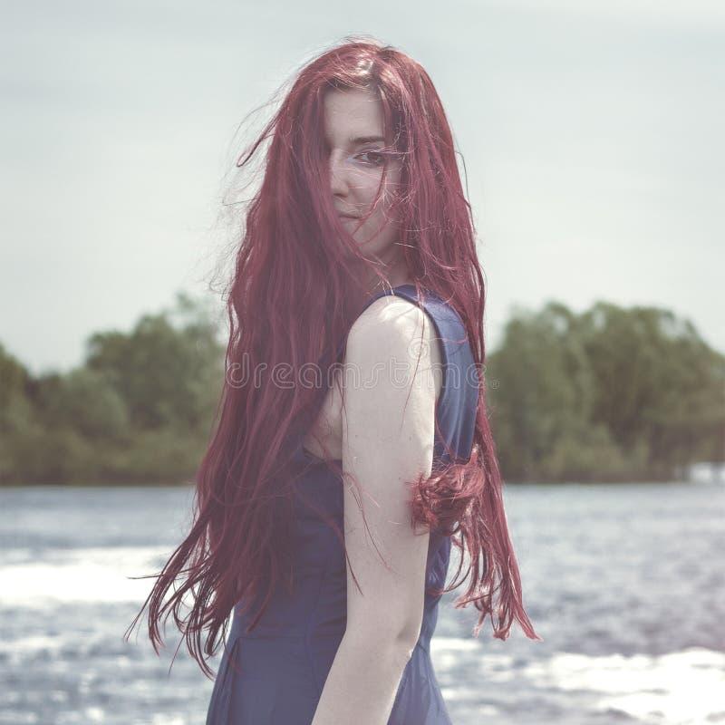Mujer pelirroja que se coloca en el río fotografía de archivo