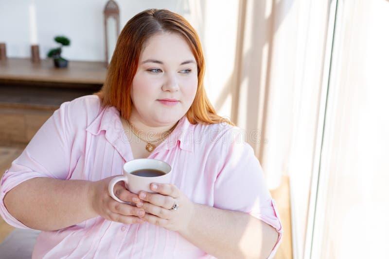 Mujer pensativa agradable que sostiene una taza de t? imagen de archivo