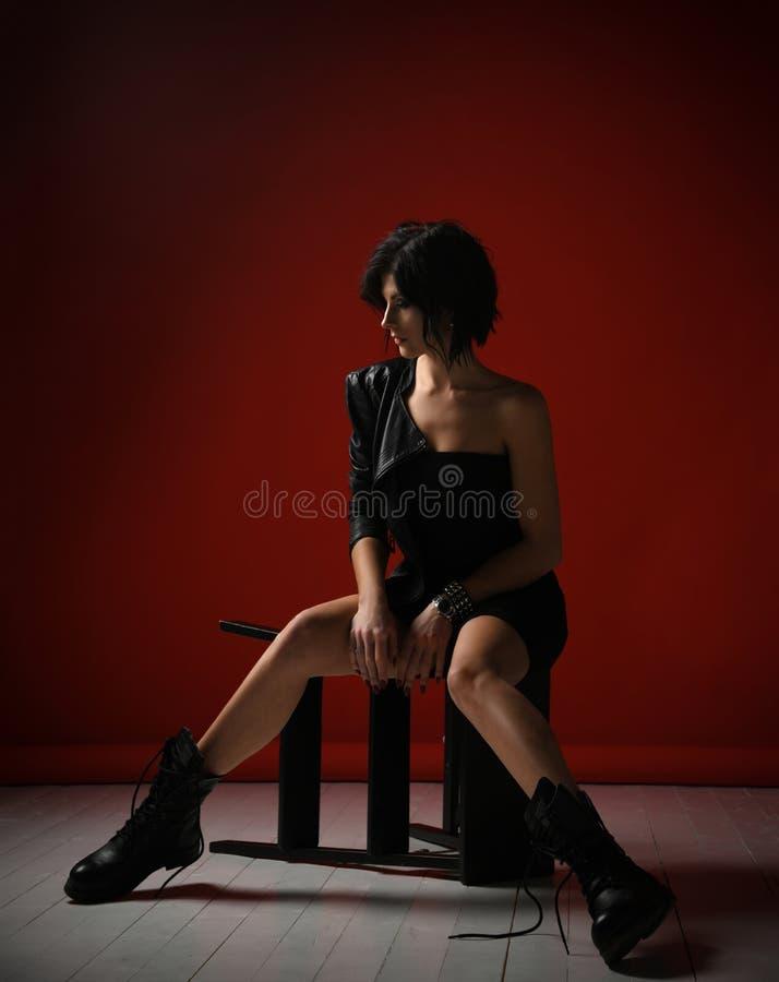 Mujer pensativa atractiva en el vestido apretado negro, la chaqueta de cuero y las botas brutales grandes sentándose en una escal foto de archivo