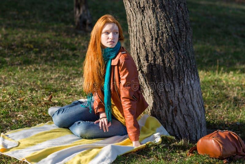 Mujer pensativa atractiva joven que se sienta debajo del árbol fotos de archivo