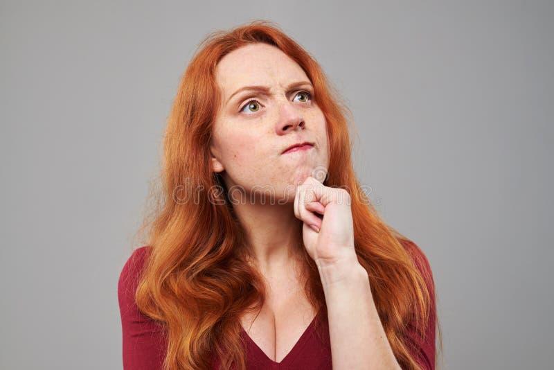 Mujer pensativa con el pelo rojo que rasguña la barbilla fotografía de archivo libre de regalías