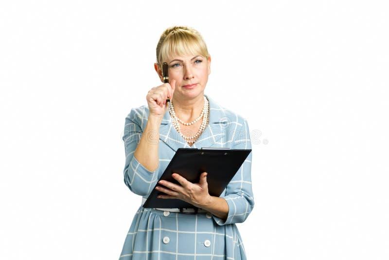 Mujer pensativa con el tablero y la pluma imagen de archivo