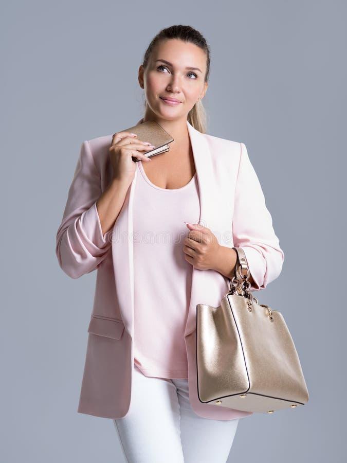 Mujer pensativa con la cartera a disposición y un bolso foto de archivo