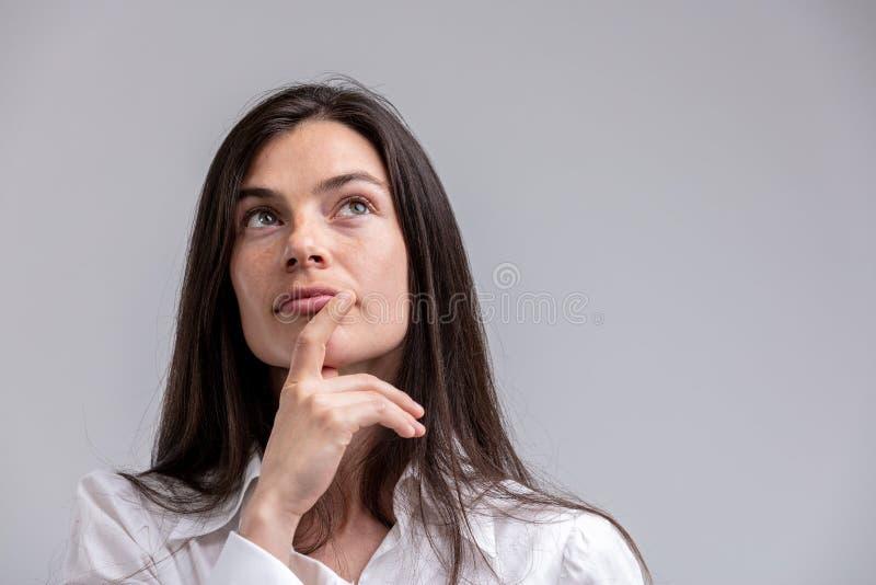 Mujer pensativa con su mano a su barbilla foto de archivo libre de regalías
