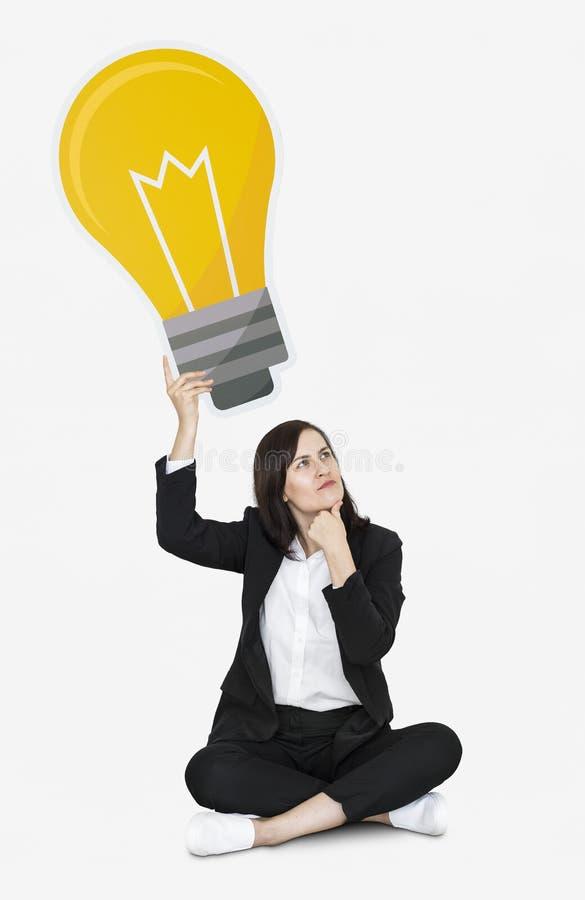 Mujer pensativa con un icono de la bombilla foto de archivo libre de regalías
