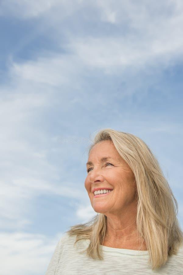 Mujer pensativa contra el cielo nublado fotos de archivo libres de regalías