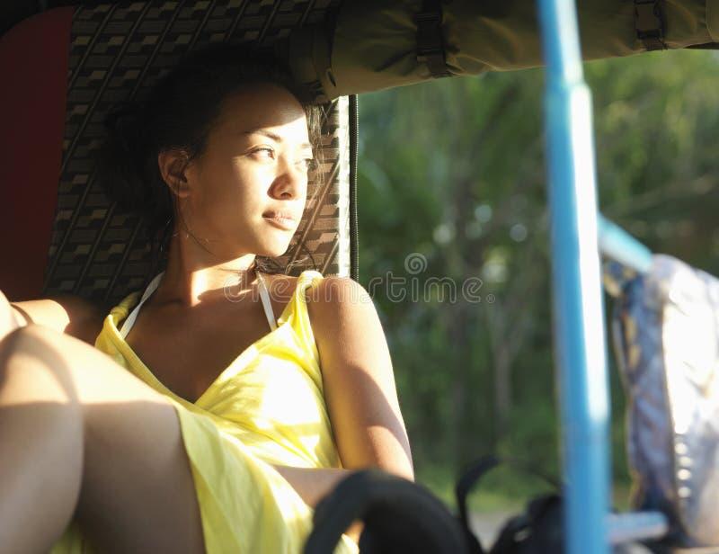 Mujer pensativa de la raza mixta en carrito foto de archivo