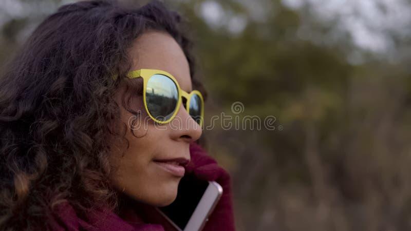 Mujer pensativa de la raza mixta en gafas de sol amarillas que habla en el smartphone, primer foto de archivo libre de regalías