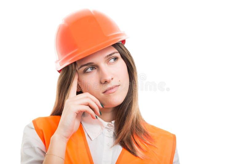 Mujer pensativa del constructor que mira lejos para encontrar la solución fotografía de archivo libre de regalías