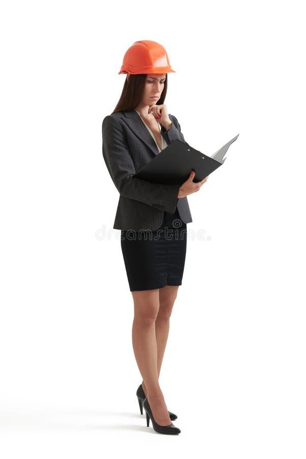 Mujer pensativa del ingeniero en el casco de protección anaranjado imagenes de archivo