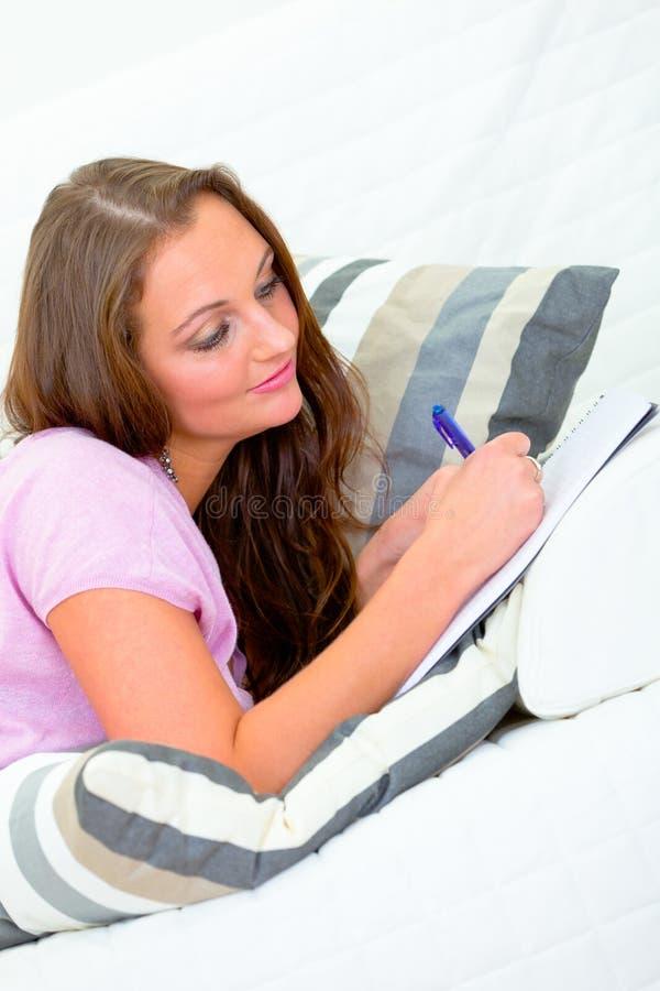 Mujer pensativa en el sofá y la escritura en cuaderno imagen de archivo libre de regalías
