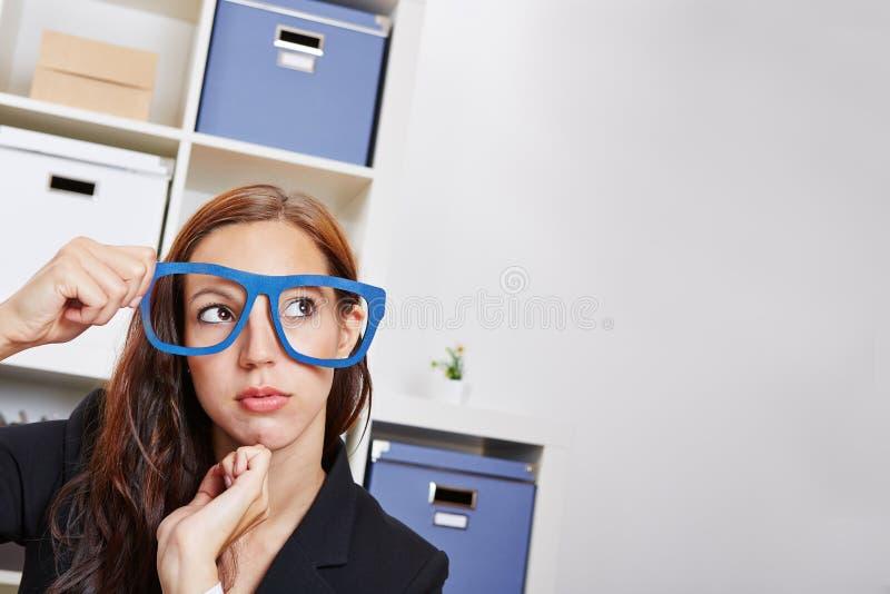 Mujer pensativa en oficina con el empollón foto de archivo