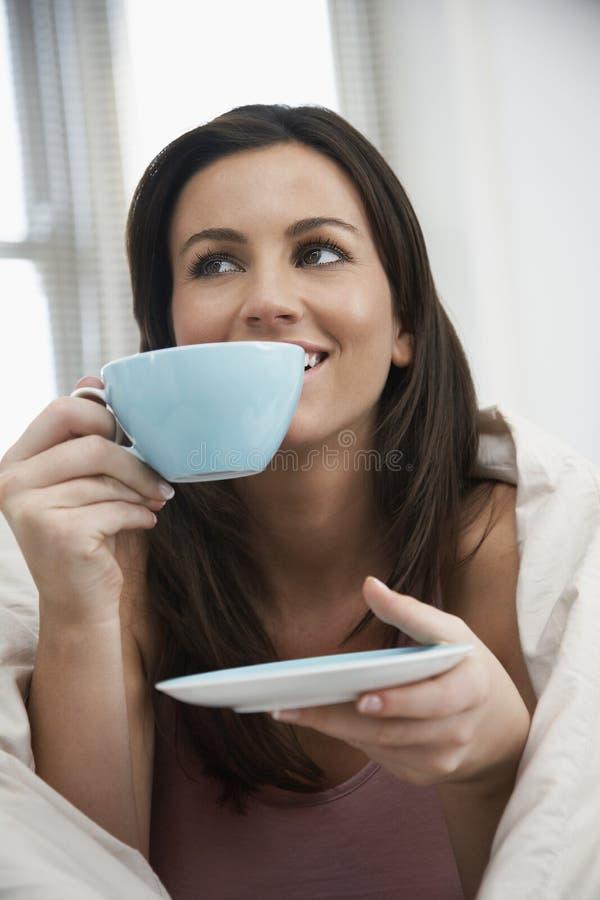 Mujer pensativa envuelta con té de consumición del edredón imagenes de archivo