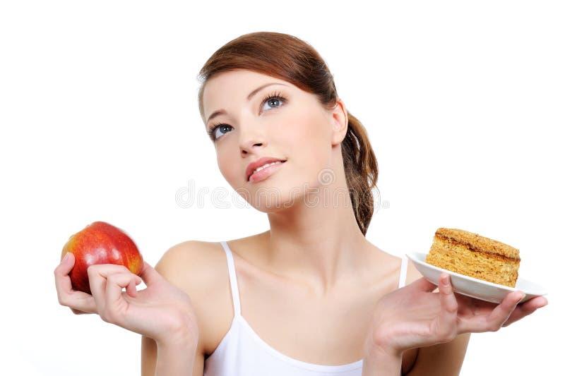 Mujer pensativa hermosa con el alimento foto de archivo libre de regalías