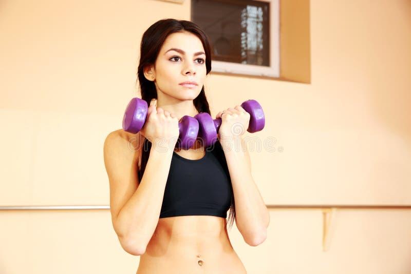 Mujer pensativa joven del ajuste que hace ejercicios con los dumbells imagen de archivo