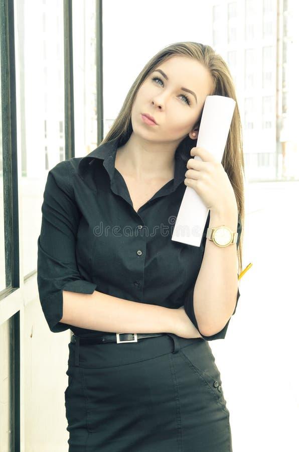 Mujer pensativa joven que se coloca con los documentos comerciales fuera del edificio de oficinas fotografía de archivo