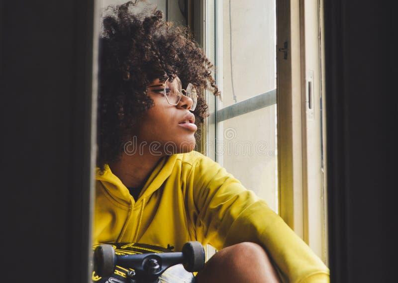 Mujer pensativa negra sensual joven elegante que se sienta cerca de la ventana con un monopatín foto de archivo