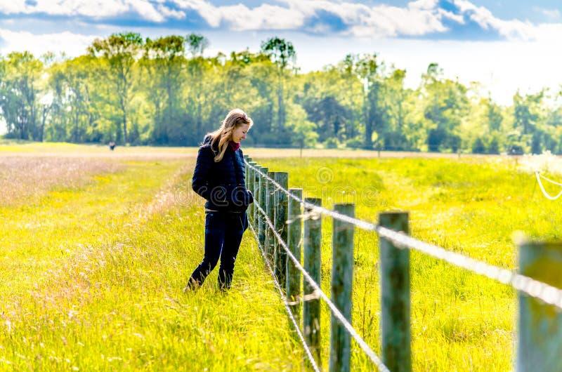 Mujer pensativa por una cerca del campo fotos de archivo libres de regalías