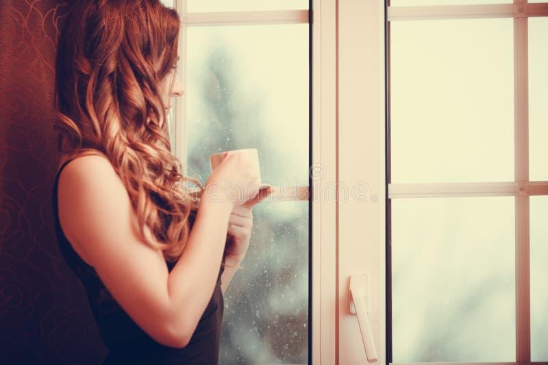 Mujer pensativa que bebe la bebida caliente del café en casa imágenes de archivo libres de regalías