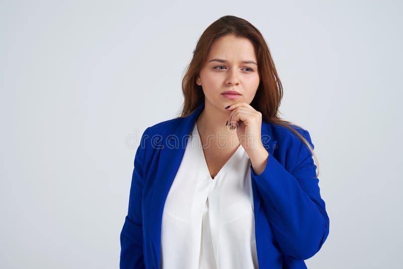 Mujer pensativa que lleva a cabo la mano en la barbilla y que parece pensativa fotos de archivo libres de regalías
