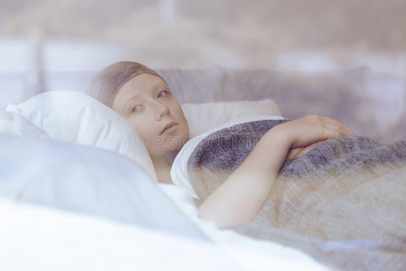 Mujer pensativa que lucha con el tumor que miente en cama del hospicio foto de archivo