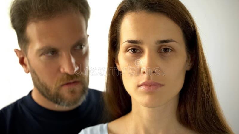 Mujer pensativa que mira al hombre de la cámara detrás de la esposa, incapacidad para tomar propias decisiones foto de archivo