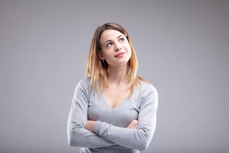 Mujer pensativa que mira diagonalmente hacia arriba fotografía de archivo