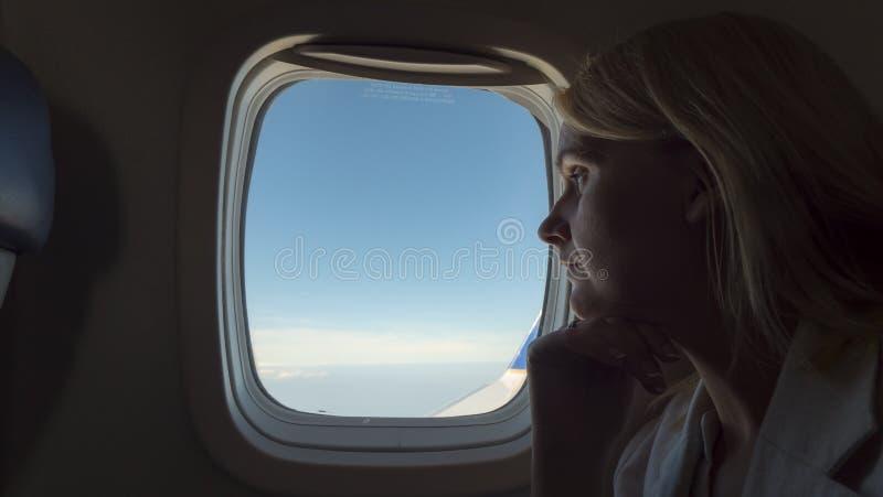 Mujer pensativa que mira hacia fuera la ventana de un aeroplano imagenes de archivo