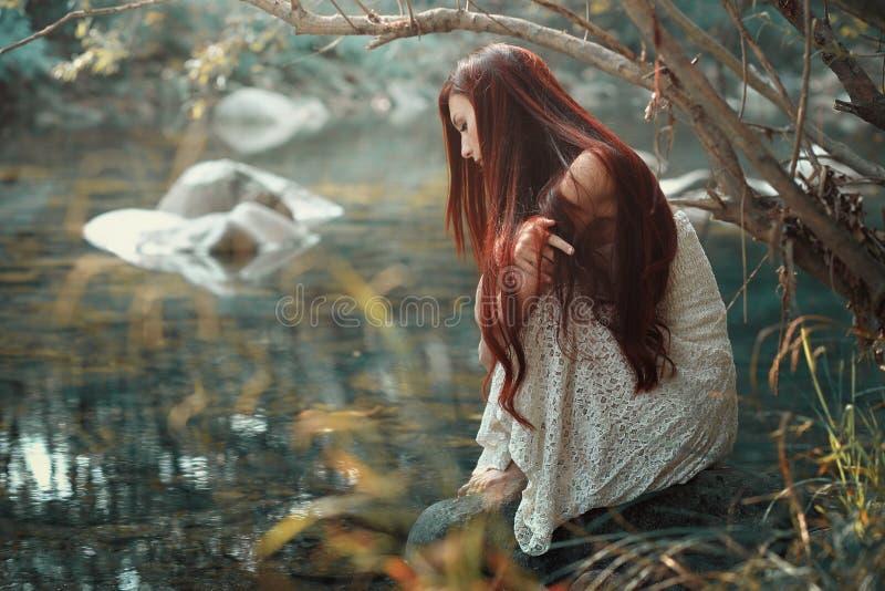Mujer pensativa que mira las aguas de la corriente imagen de archivo
