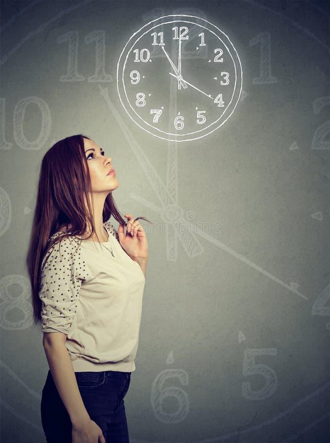Mujer pensativa que mira para arriba el reloj fotos de archivo libres de regalías