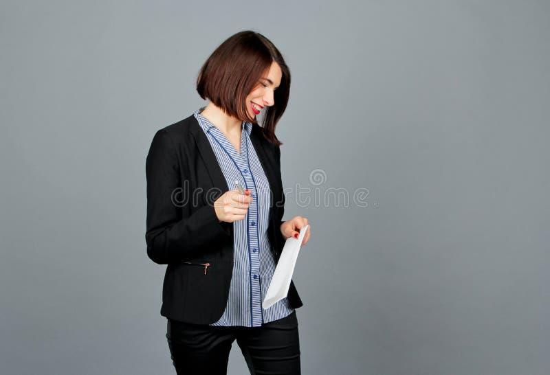 Mujer pensativa que parece ausente mientras que sonrisa Escriba en notas imágenes de archivo libres de regalías