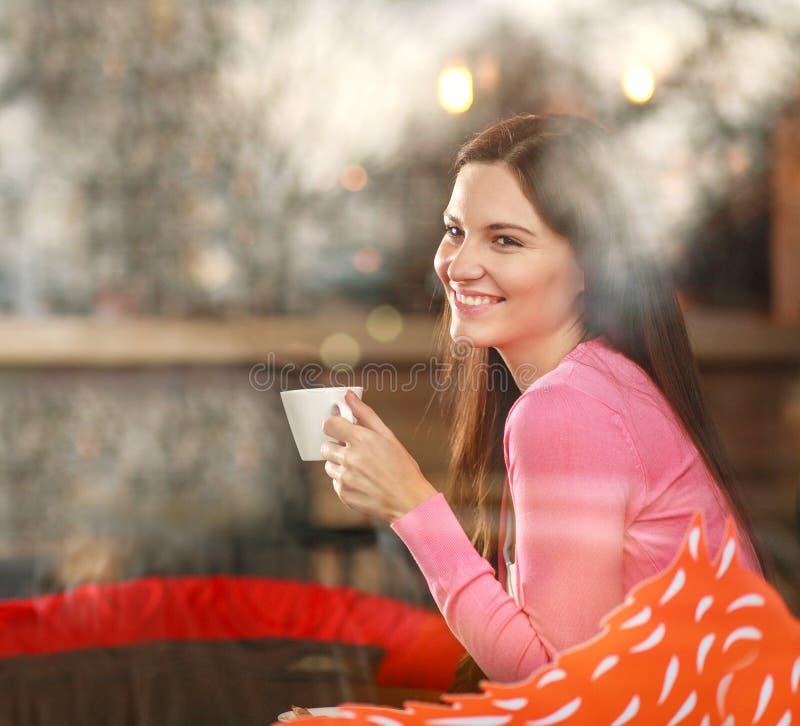 Mujer pensativa soñadora sonriente en restaurante con la taza de café, alegre mirando hacia fuera, visión a través de ventana con foto de archivo libre de regalías