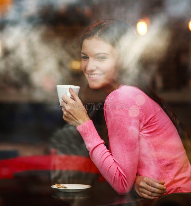 Mujer pensativa soñadora sonriente en restaurante con la taza de café, alegre mirando hacia fuera, visión a través de ventana con fotos de archivo libres de regalías