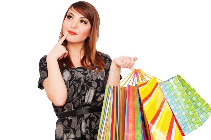 Mujer pensativa sonriente con los bolsos de compras imagen de archivo libre de regalías