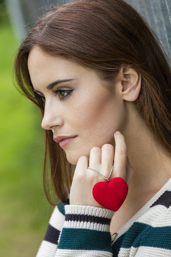 Mujer pensativa triste con el collar rojo del corazón fotografía de archivo libre de regalías