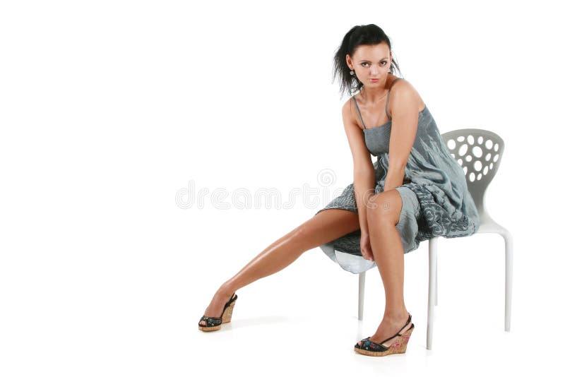 Mujer pequeña joven en una alineada gris en una silla foto de archivo