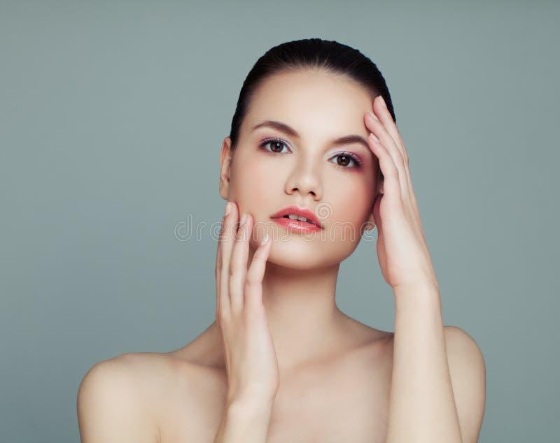 Mujer perfecta con la piel clara en fondo gris imagen de archivo